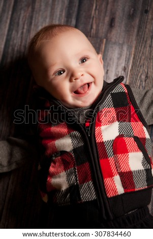 An adorable 5 month old baby boy on a black background.