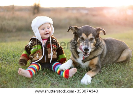 An adorable 8 month old baby girl is bundled up in a sweater and wearing a winter earflap hat looking lovingly at her pet German Shepherd dog as they sit and laugh outside on a cold fall day. - stock photo