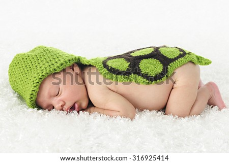 An adorable newborn sleeping contentedly on a fluffy blanket and covered with a hand-knit turtle hood and back.   On a white background - stock photo