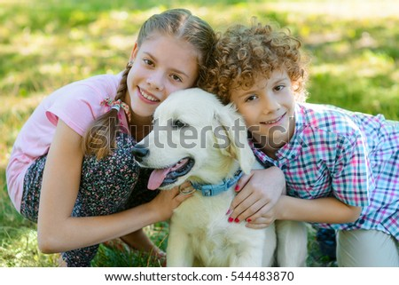 An adorable portrait of the best friends - lovely girl, redhead boy and their dog. Children embrace golden retriever with his tongue out and look right in the camera with cute smiles.
