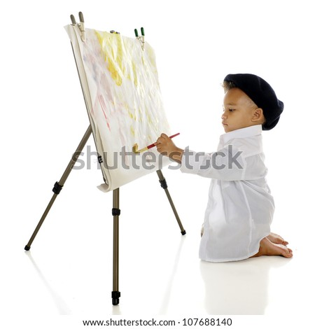 An adorable preschool artist painting on an easel in his French beret and smock.  White background. - stock photo