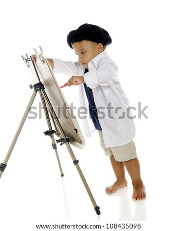 An adorable preschool artist painting on an easel in his French beret and white smock.  On a white background.