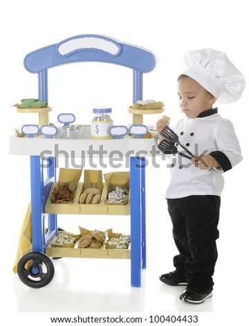 "An adorable preschool ""baker"" snitching cookies from his vendor cart.  On a white background.  Signs left blank for your text."
