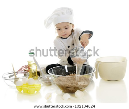 "An adorable preschool ""chef"" dumping water from a measuring cup into the chocolate cake mix in a clear bowl. - stock photo"