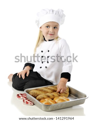 "An adorable preschool ""chef"" sitting on the floor displaying fresh loaves of bread and buns in a pan.  On a white background."