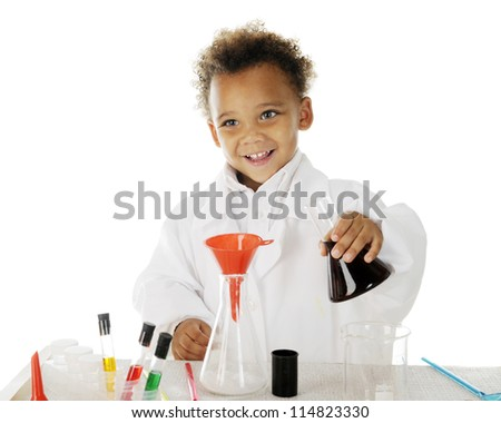 "An adorable preschool ""chemist"" happily preparing to pour a dark liquid from one glass flask into another."