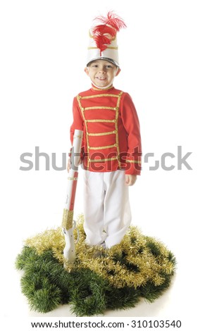 An adorable preschool Christmas soldier smiling as he stands straight and tall with his rifle.  He's surrounded by green and gold garland.  On a white background. - stock photo