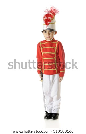 """An adorable preschool """"Christmas soldier"""" standing straight and tall with a sword by his side.  On a white background. - stock photo"""