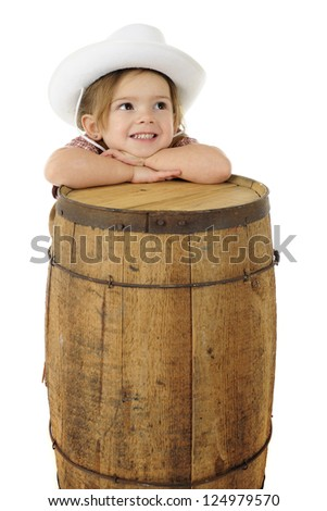 An adorable preschool cowgirl resting her head on a rustic wood barrel.  On a white background with space for your text on the barrel. - stock photo