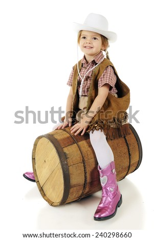 "An adorable preschool cowgirl ""riding"" an old wooden barrel.  On a white background. - stock photo"