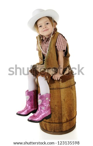 An adorable preschool cowgirl sitting pretty on an old barrel.  On a white background. - stock photo