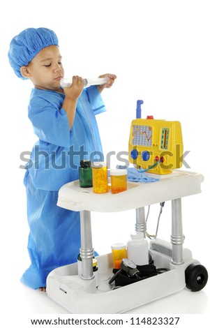 "An adorable preschool ""doctor"" in blue scrubs checking the measurements on a large syringe as he stands by an emergency cart.  On a white background."
