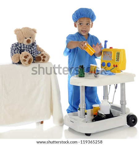 "An adorable preschool ""doctor"" in blue scrubs questioning about the medication he should be giving his patient (toy bear) from his emergency cart.  On a white background. - stock photo"