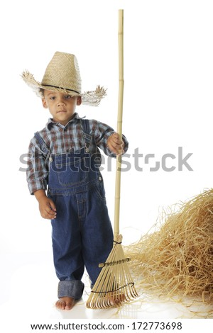 "An adorable preschool ""farmer"" standing by a haystack -- barefoot and with a rake.  On a white background."