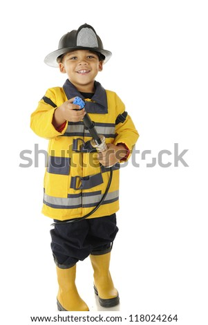"An adorable preschool ""fire chief"" in full gear.  He's happily aiming his hose.  On a white background. - stock photo"