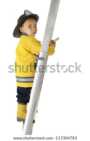"An adorable preschool ""Fire Chief"" looking back at the viewer as he climbs a ladder with his fire hose.  On a white background."