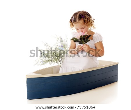 An adorable preschool girl smelling a large, pink flower deeply.  Isolated on white. - stock photo