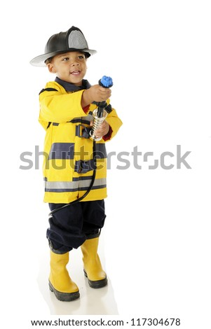 "An adorable preschool in full ""Fire Chief"" gear aiming his hose toward a (pretend) fire.  On a white background. - stock photo"