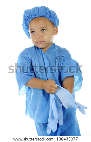 "An adorable preschool ""surgeon"" in blue scrubs donning his surgical gloves.  On a white background."