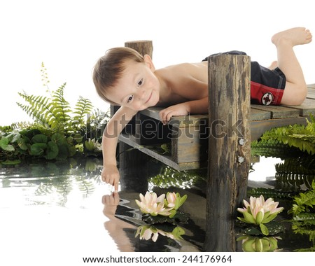 """An adorable preschool """"swimmer"""" laying on an old dock, checking the water's temp with his finger.  On a white background. - stock photo"""