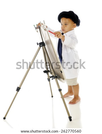 An adorable preschooler concentrating as he paints on an easel in his smock and French beret.  On a white background. - stock photo