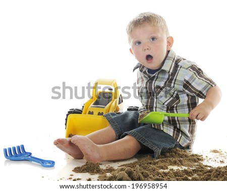 An adorable preschooler expressing surprise while playing in sand with his toy bulldozer.  On a white background. - stock photo
