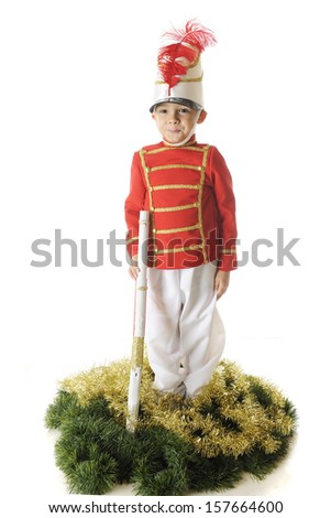 An adorable preschooler, handsome standing straight and tall in his Christmas soldier uniform with a white gun and surrounded by green and gold garland.  On a white background. - stock photo