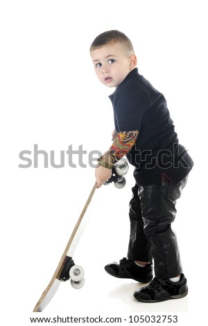 An adorable preschooler in black leather and arm tattoos, looking worried that he's been caught pulling out a skateboard.