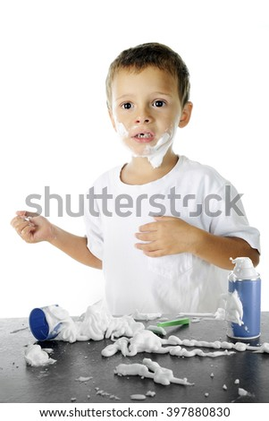 An adorable preschooler looking worried in the midst of the shaving cream mess he's made as he attempts to shave like his dad.  On a white background. - stock photo