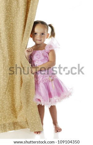 An adorable preschooler peeking from behind a curtain in her pink princess dress.  On a white background. - stock photo