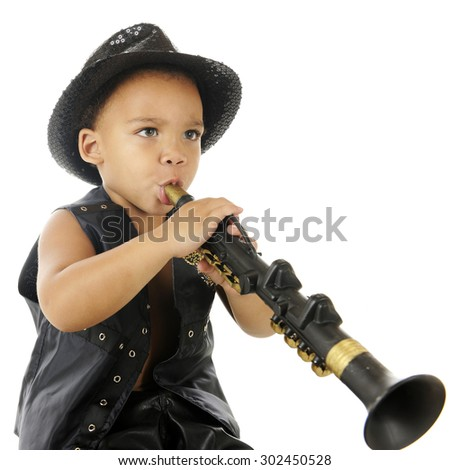 An adorable preschooler playing a toy clarinet (upside down) in his sparkly fedora and black leather vest.  On a white background.