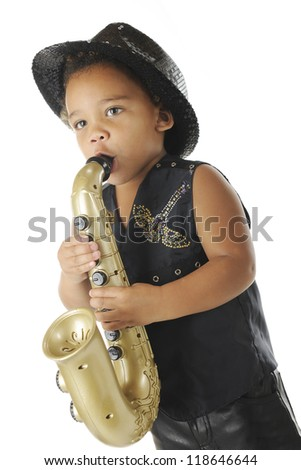 An adorable preschooler playing a toy saxophone in a sparkly black fedora and black leather vest and pants.  On a white background. - stock photo