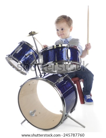 An adorable preschooler playing on a drum set.  On a white background. - stock photo