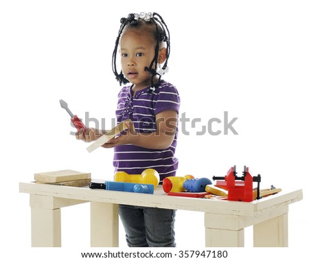 An adorable preschooler playing with the toy tools on a  workbench.  Taken on a white background. - stock photo
