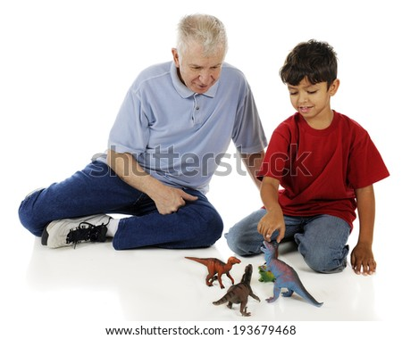 An adorable preschooler showing his grandpa his collection of toy dinosaurs.  On a white background. - stock photo
