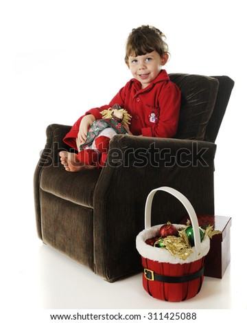 An adorable preschooler sitting in a plush chair in her red pajamas.  She holds a doll in a Christmas dress and a basket of ornaments sits at her side.  On a white background. - stock photo