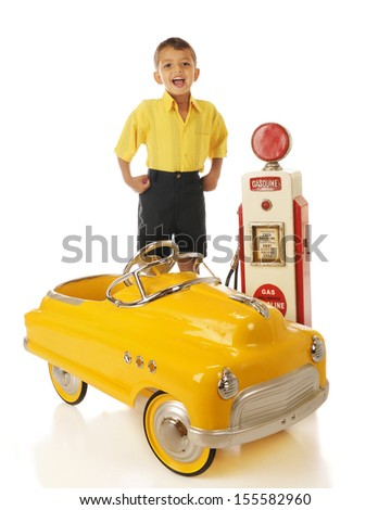 An adorable preschooler standing by a model old gas pump with his yellow pedal car.  On a white background. - stock photo
