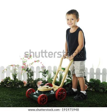 An adorable preschooler standing on grass with his toy lawnmower.  The grass is edged by a short fence and foliage, on a white background. - stock photo