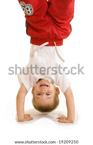 An adorable three year old doing a handstand.
