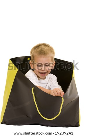 An adorable three year old playing with a shopping bag, isolated on white.