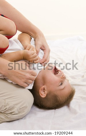 An adorable three year old playing with his mother. - stock photo