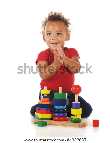 "An adorable toddler clapping for himself for ""successfully"" assembling a colorful stacking toy.  On a white background.  Motion blur on child's hands."