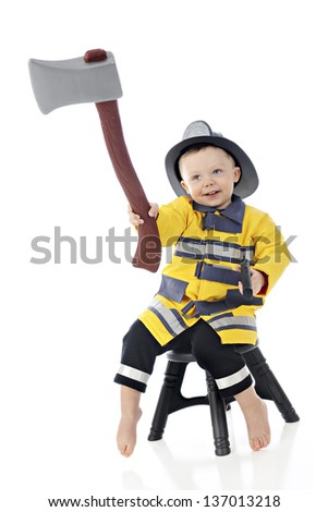 """An adorable toddler """"fireman"""" holding his hatchet high while sitting on a stool.  On a white background. - stock photo"""