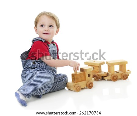 An adorable toddler in pin striped overalls as he pulls the engine of a wooden toy train.  On a white background. - stock photo