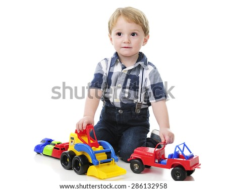 An adorable toddler looking up as he plays with her cars and trucks.  On a white background.