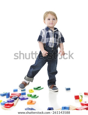 An adorable toddler navigating over a floor strewn with colorful  blocks and stack toys. - stock photo