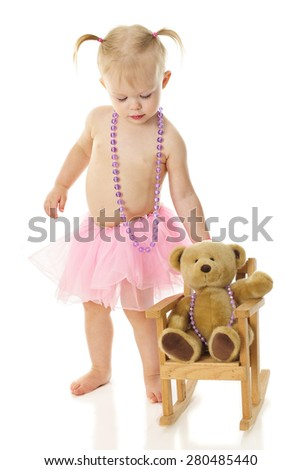 An adorable toddler wearing a necklace and tutu rocking her toy bear who wears a similar necklace.  On a white background. - stock photo