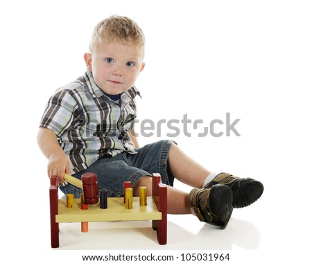 An adorable tot happily playing with a peg and hammer toy.  On a white background.
