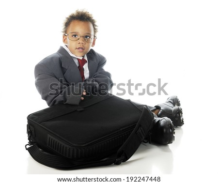 An adorable tot sitting with his computer case while dressed in an oversized business suit and dress shoes.  On a white background. - stock photo