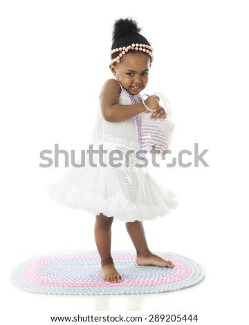 An adorable two year old looking bashful in her petticoat and pearls.  On a white background. - stock photo